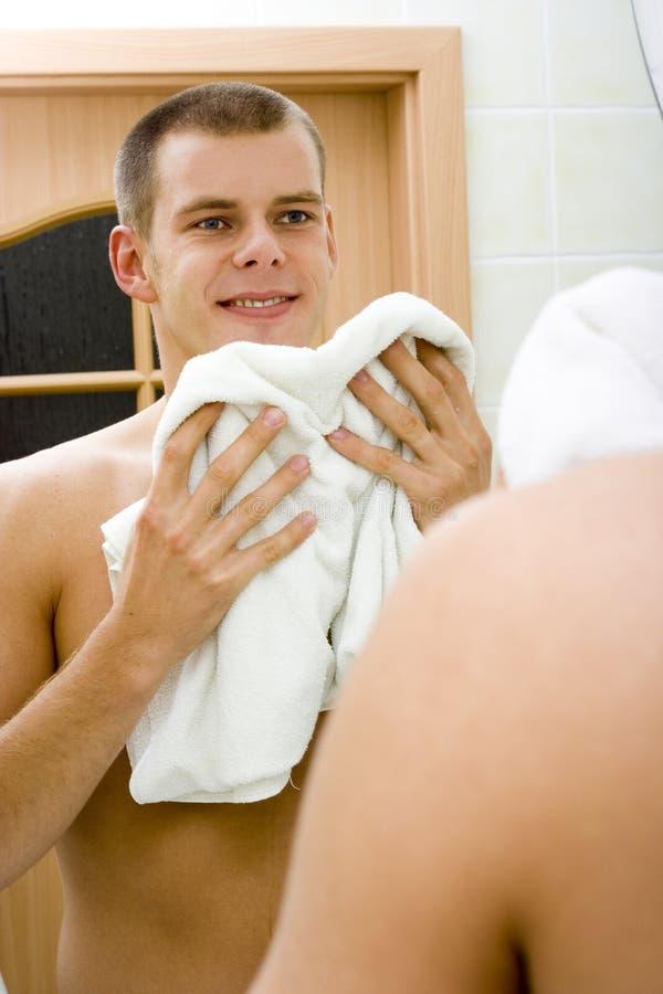 卫生间人镜子s刮脸年轻人 免版税图库摄影