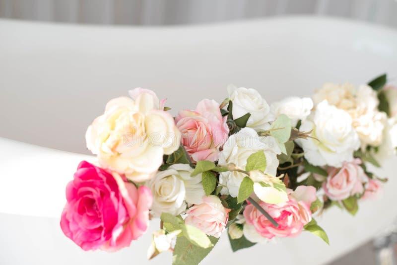 卫生间在用玫瑰的花和瓣装饰的一间轻的屋子 免版税图库摄影