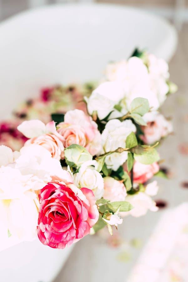 卫生间在用玫瑰的花和瓣装饰的一间轻的屋子 免版税库存照片