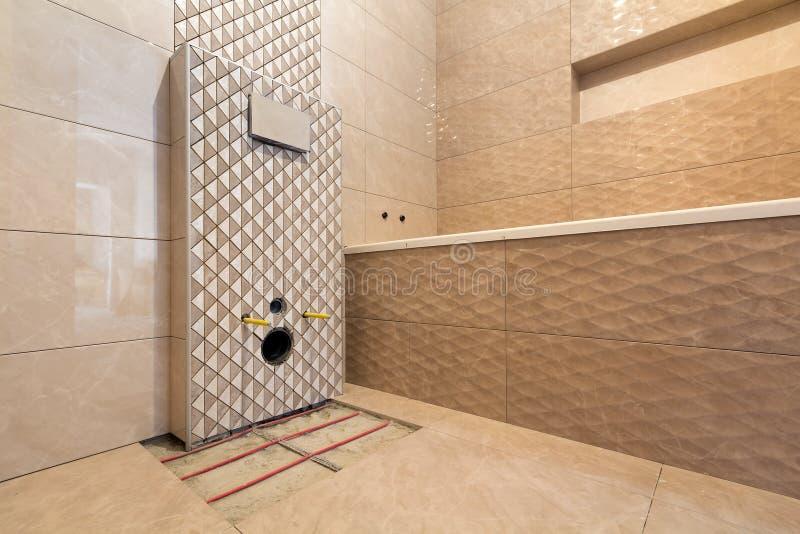 卫生间或洗手间与在墙壁安装的轻的米黄几何瓷砖,地方的未完成的重建洗手间的 免版税库存图片