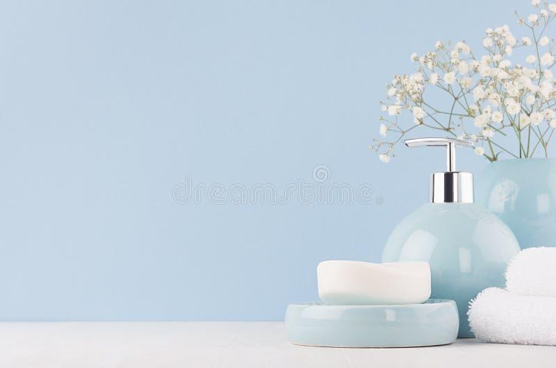 卫生间的新鲜的春天装饰有小白花、陶瓷花瓶和肥皂泵浦瓶的,在白木委员会的毛巾 库存图片