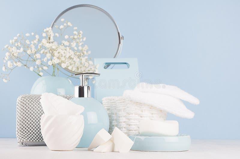 卫生间的-淡色蓝色陶瓷碗,花,镜子,在白色木头的银色化妆辅助部件现代柔光内部 免版税图库摄影