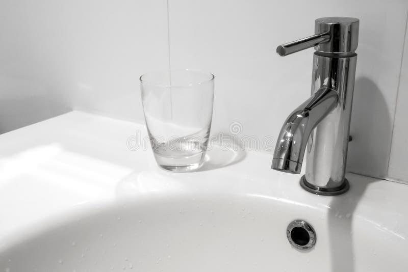 卫生间龙头和面盆与水玻璃 免版税库存图片