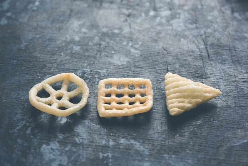 印地安嘎吱咬嚼的fryums或papad快餐在轮子、正方形和三角塑造 库存图片
