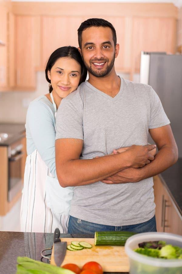 印地安夫妇拥抱厨房 免版税库存照片