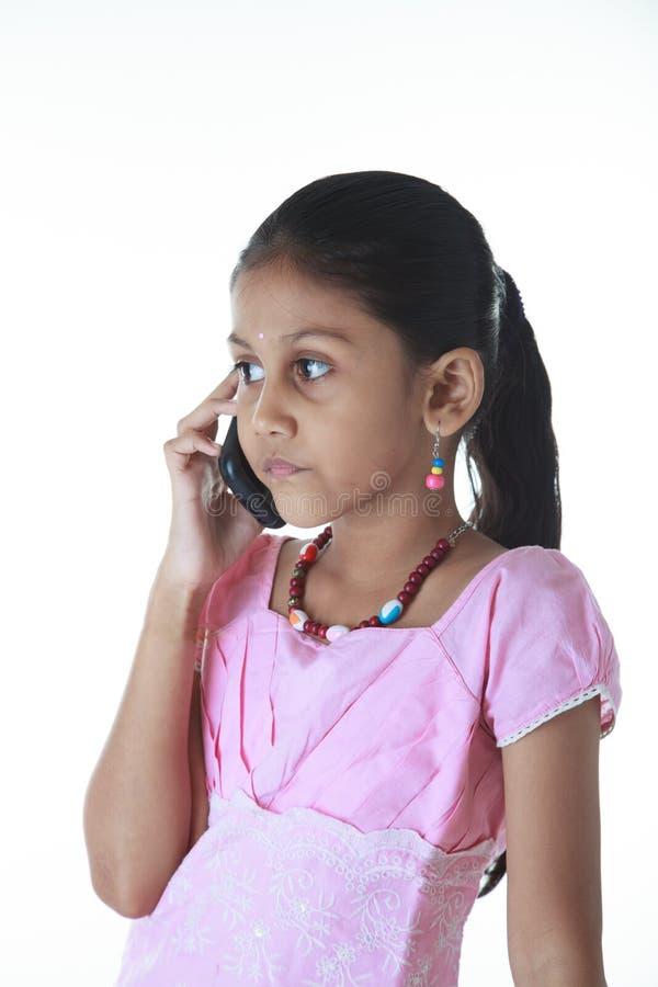 印地安女孩讲话由手机与白色背景 图库摄影