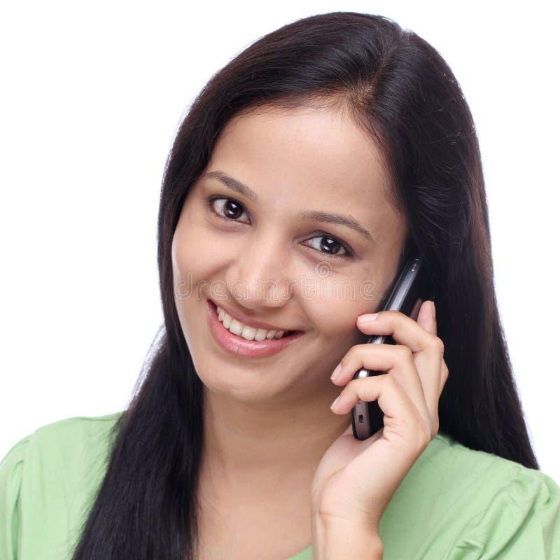 年轻印地安女孩谈话在手机 免版税库存图片