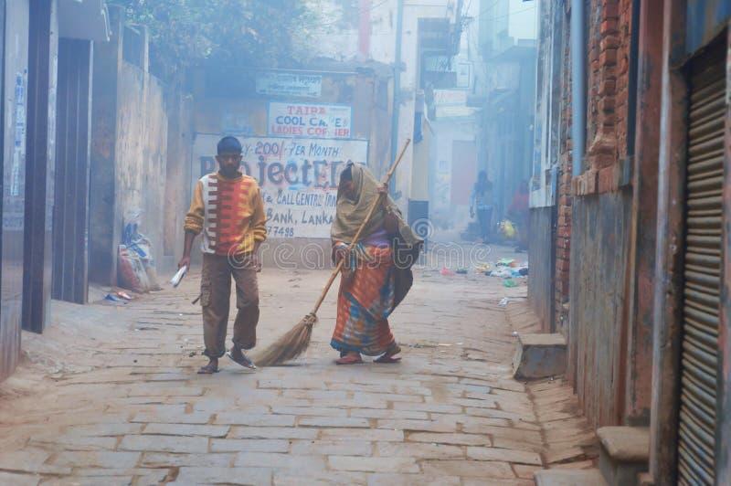 印地安妇女在瓦腊纳西清扫街道冷的有雾的冬天早晨 免版税图库摄影