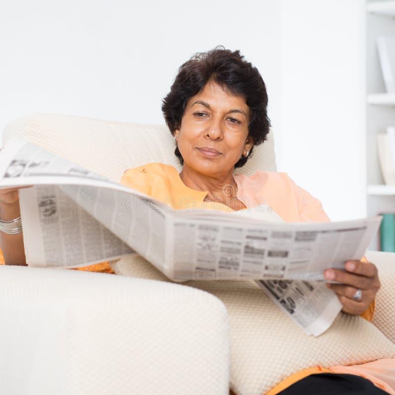 印地安成熟妇女读书新闻报纸 库存图片