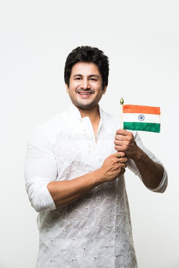 印地安英俊的男孩或人拿着印地安国旗和显示爱国心的白色种族穿戴的,站立隔绝在白色 库存照片
