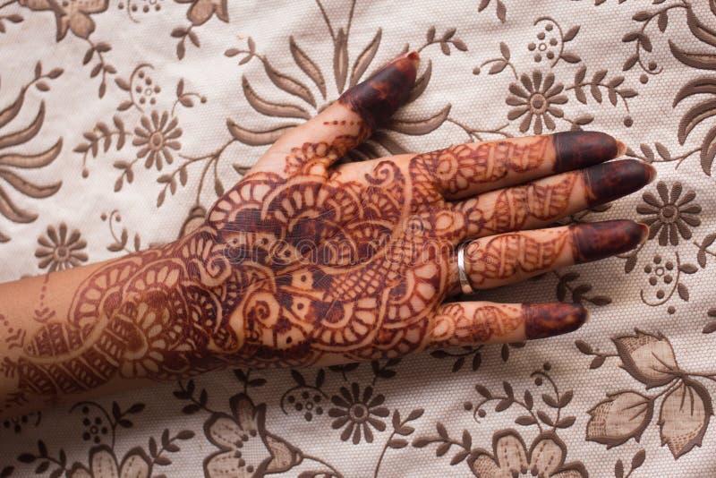 印地安mehndi (无刺指甲花绘画)在用花装饰的背景的woman's手上 库存照片
