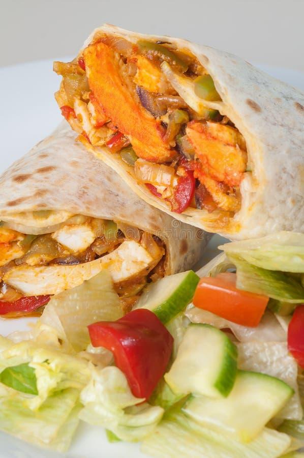 印地安tandoori鸡卷或扭转者用旁边沙拉在白色板材 库存照片