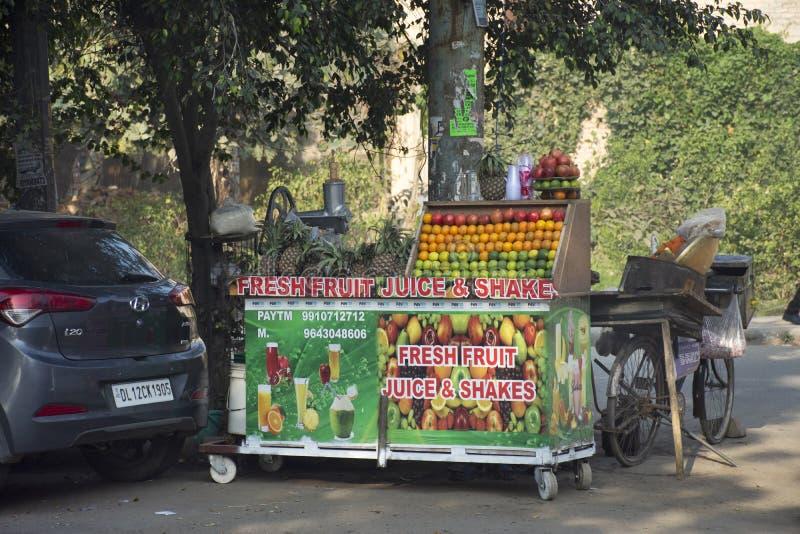 印度人销售和买汁液震动从小地方杂货摊位商店的果菜类在新德里,印度 图库摄影