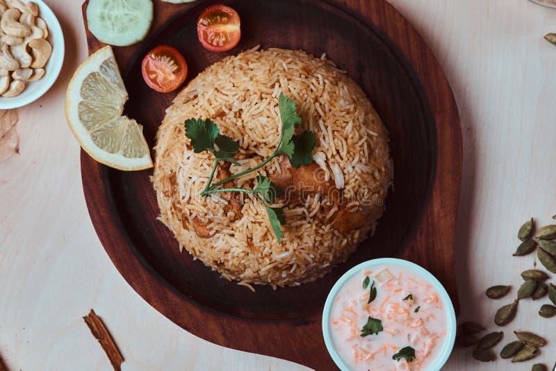 印度传统盘用米、腰果、调味汁、柠檬、菜和香菜叶子在木盘子 免版税库存照片