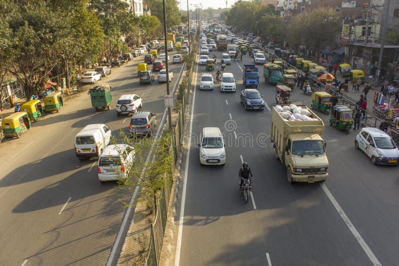 印度公路交通和边路有停放的出租汽车人力车的在各种各样的城市的街道上 免版税库存照片
