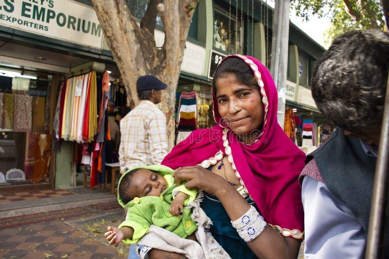印度妇女叫化子或贱民世袭的社会等级举行婴孩和乞求金钱从旅客人在新德里,印度 免版税库存图片
