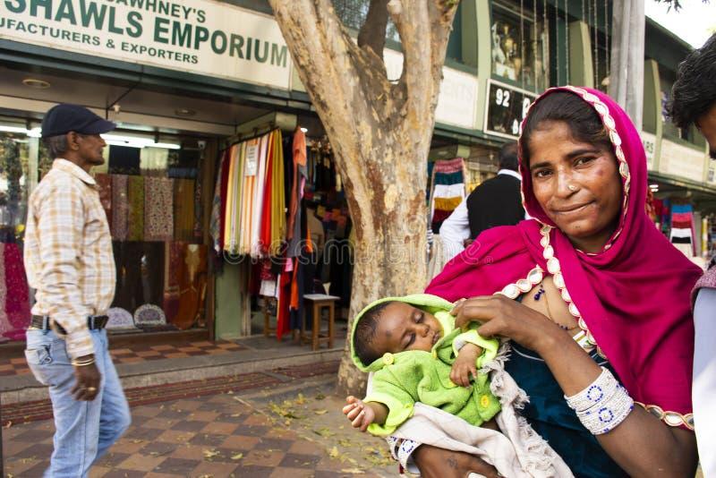 印度妇女叫化子或贱民世袭的社会等级举行婴孩和乞求金钱从旅客人在新德里,印度 免版税图库摄影