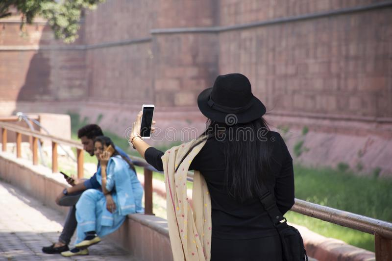 印度妇女在古城德里远航参观和旅行作为世界遗产名录站点的照片与德里红堡或奥瑟莉珀的Qila 免版税库存照片