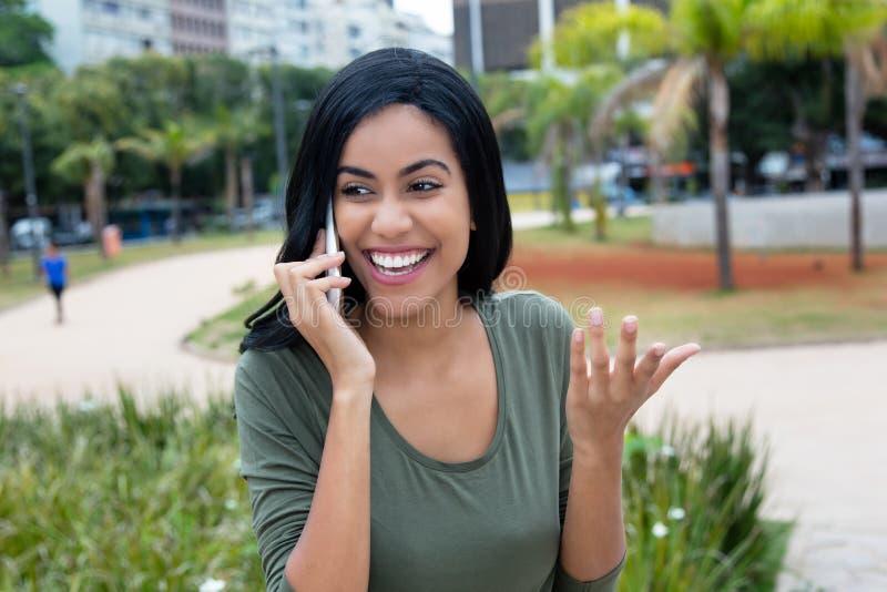 印度妇女谈话与其他妇女在电话 免版税库存图片