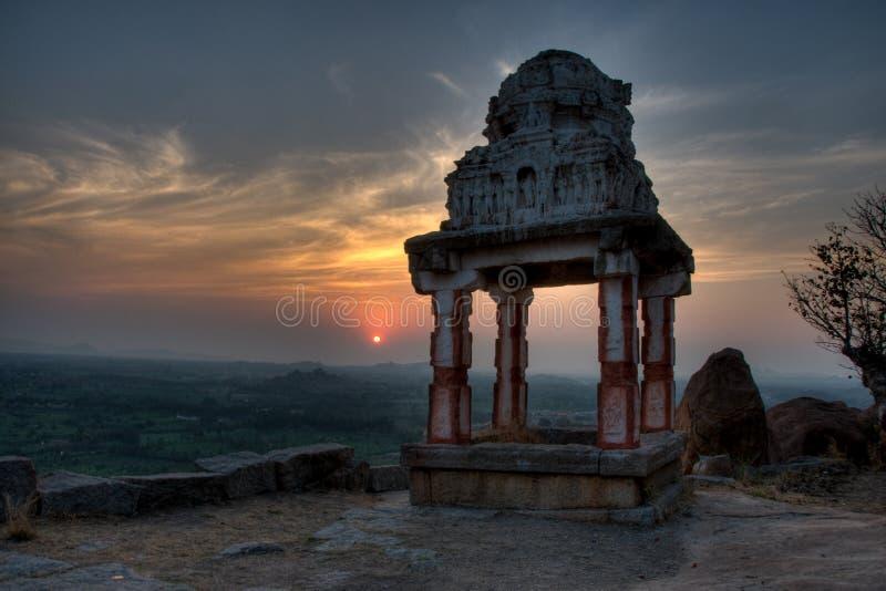 印度寺庙的老废墟在半剪影的与落日在背景中 库存照片