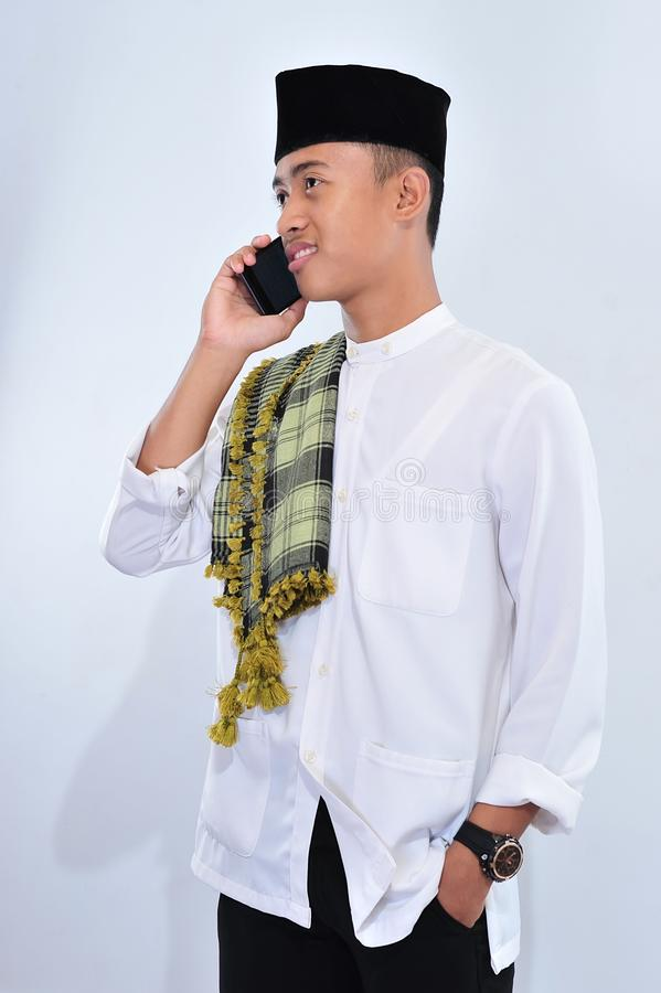 印度尼西亚回教商人画象在传统衣裳的谈话在电话 库存图片