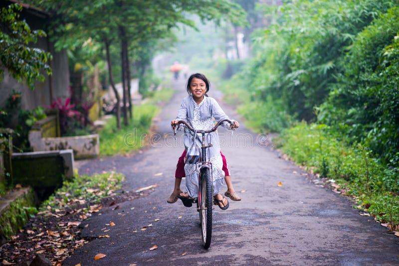 印度尼西亚女孩孩子乘驾bycyle 库存照片