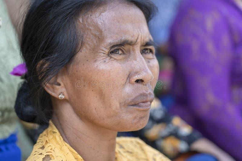 印度尼西亚妇女祷告在期间在Ubud,海岛巴厘岛,印度尼西亚出了价在中央街道上的火葬仪式 图库摄影