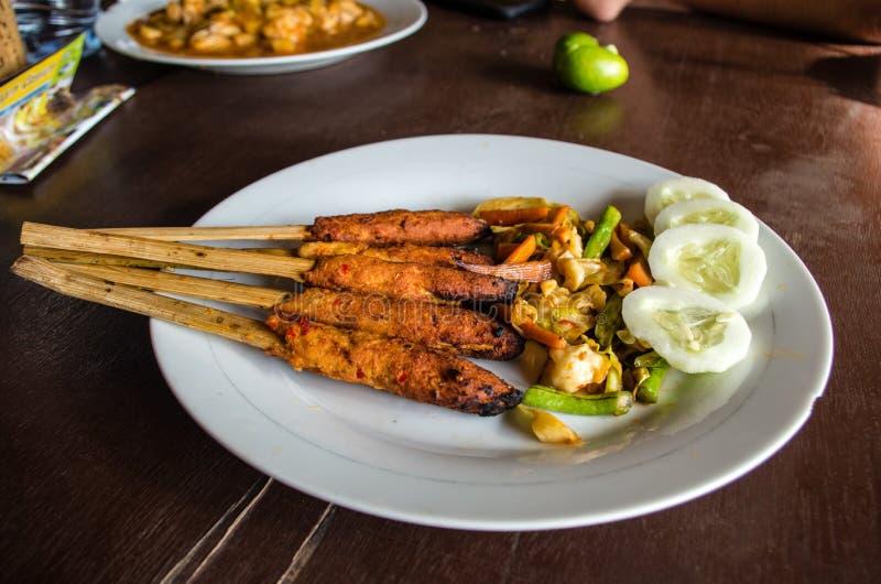 印度尼西亚盘龙目岛:心满意足Pusut在棍子的用卤汁泡的肉混合在与其他盘的桌上在背景中 免版税库存图片