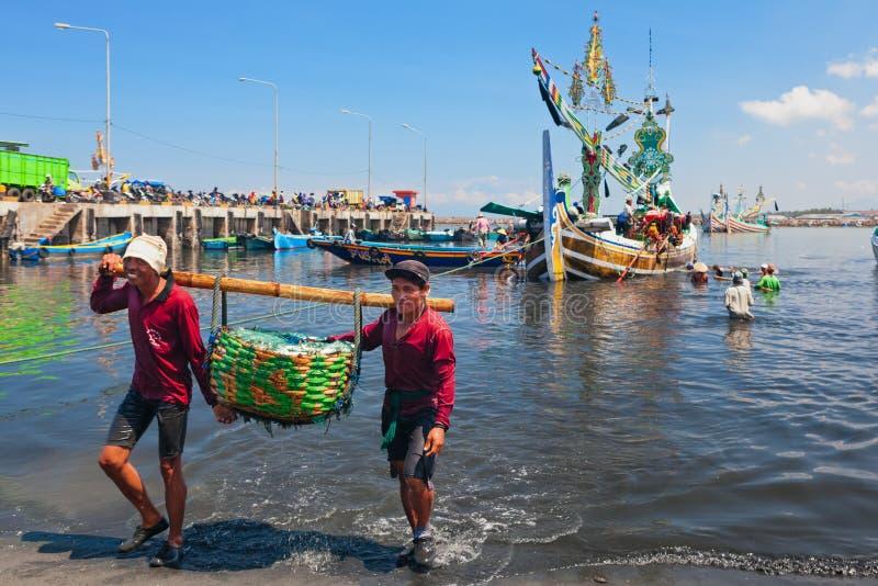 印度尼西亚码头工人卸载传统渔船 库存图片