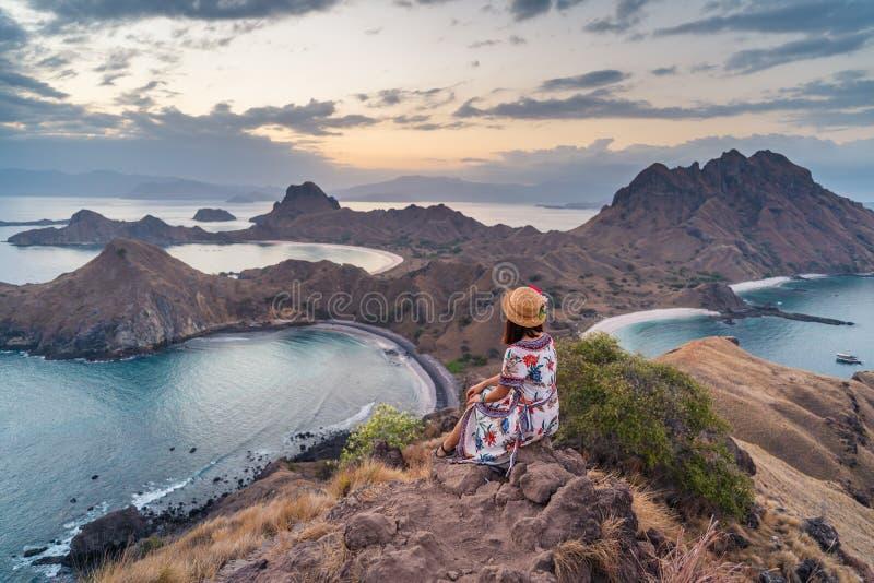 印度尼西亚科莫多国家公园的帕达尔岛日落时,年轻游客坐在岛上放松 免版税库存图片