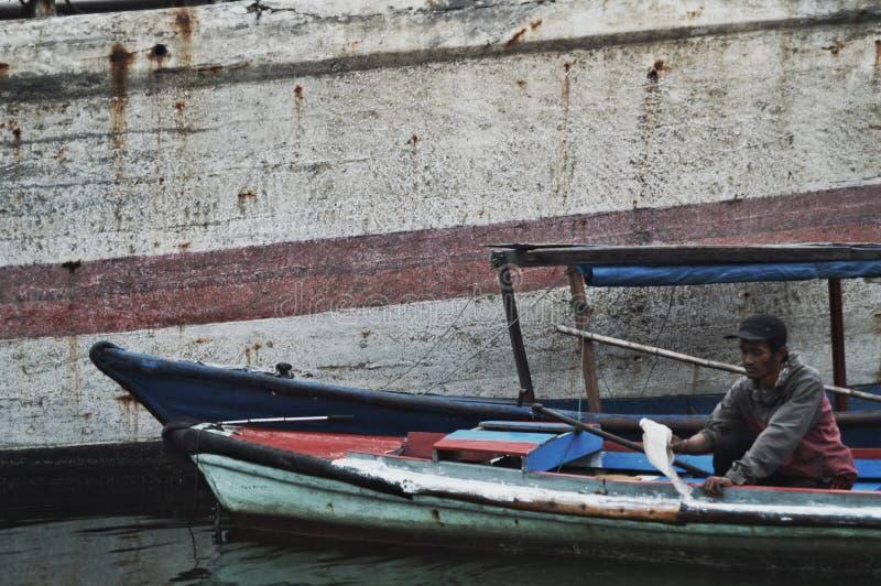 印度尼西亚雅加达 — 2018年10月12日:一个渔民在阴天的下午工作,家人在家里等 免版税库存图片