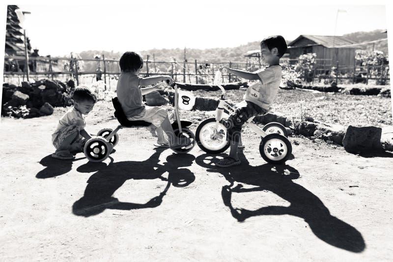 印度尼西亚,巴厘岛- 2014年8月:一个小组不明身份的孩子在他们的自行车使用 从未开展的国家的孩子居住 库存图片