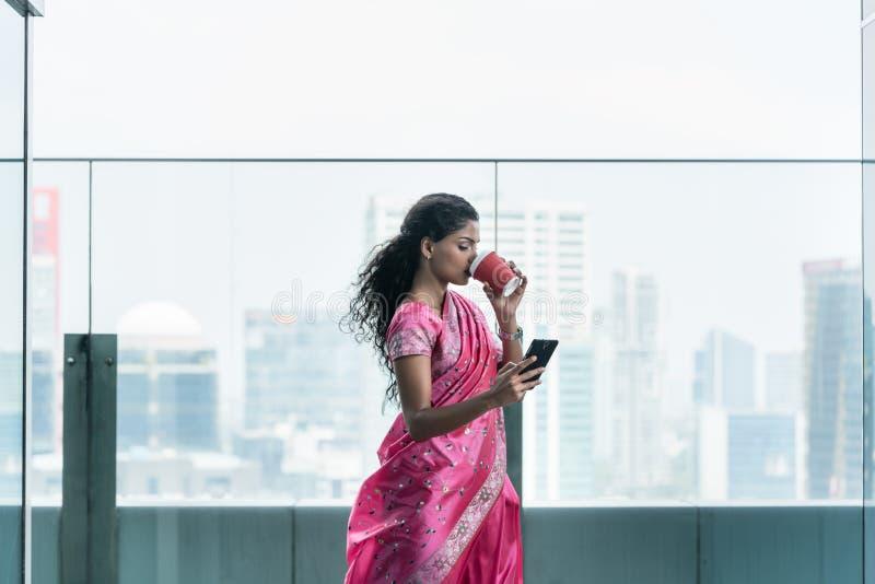 印度年轻女人饮用的咖啡,当使用一个手机时 库存图片