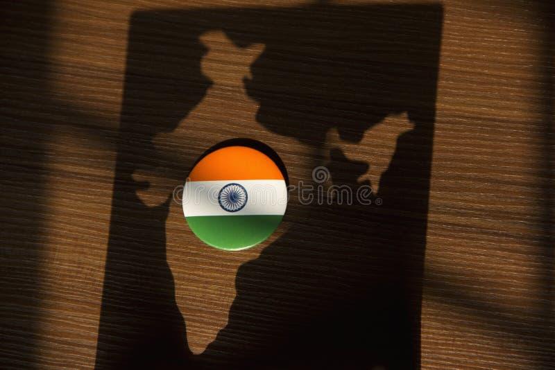 印度旗子徽章在棕色背景保留在印度地图的阴影 免版税库存照片