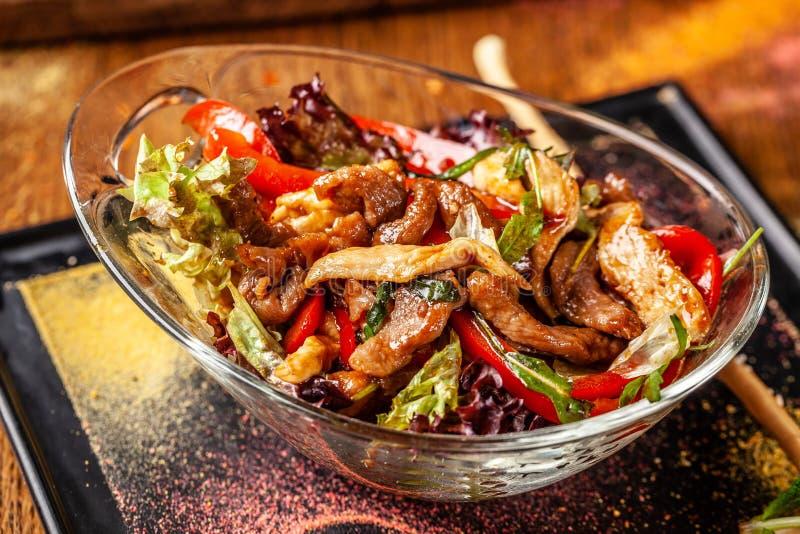 印度烹调的概念 温暖的沙拉用牛肉和鸡、甜椒和蜂蜜薄荷调味料 大盘子在餐馆 免版税库存照片