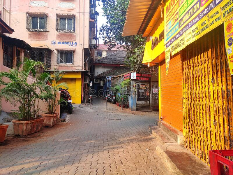 印度班德拉孟买一条空荡荡的街道,白天有黄色商店和植物 免版税库存图片