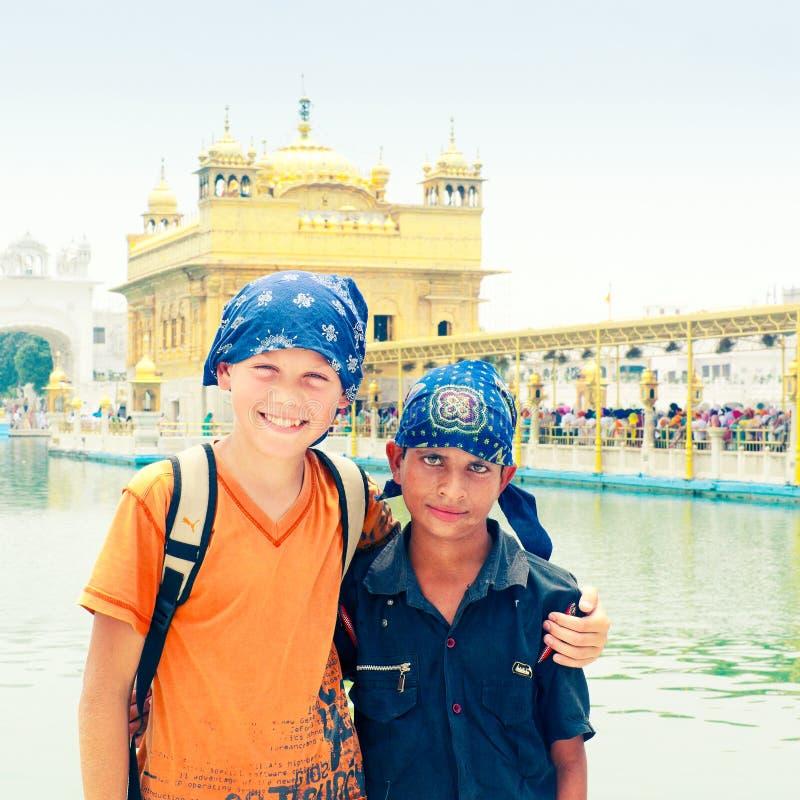 印度男孩,年轻锡克教徒的香客站立拥抱与他的在金黄寺庙-主要锡克教徒的寺庙复合体对面的欧洲朋友- Gurudwa 免版税库存照片