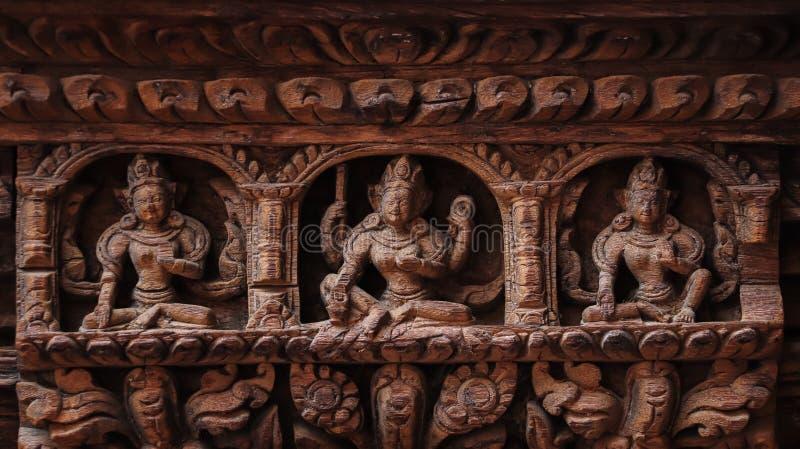 印度神和女神雕象在木门雕刻了 免版税库存图片
