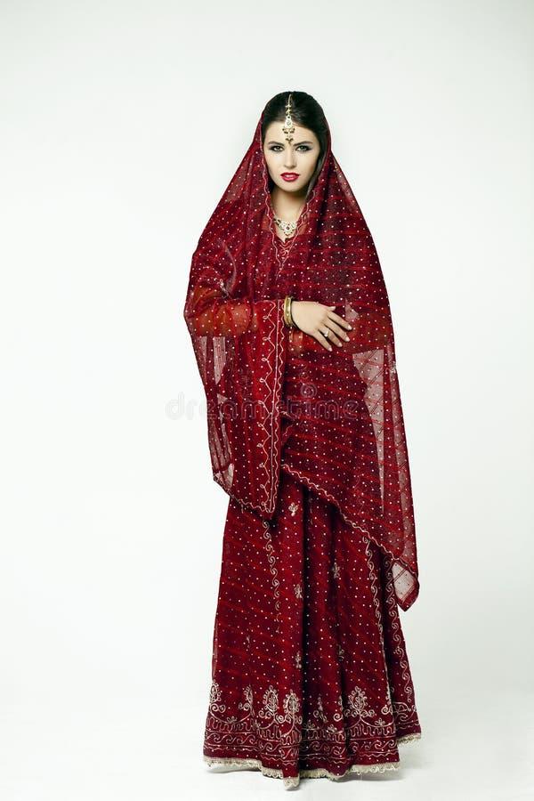印度红礼服的年轻俏丽的妇女 免版税库存图片