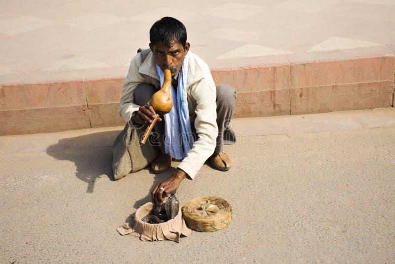 印度耍蛇者戏剧和眼镜蛇蛇迷人的展示在街道上印度人民和外国旅客的印度门的 库存图片