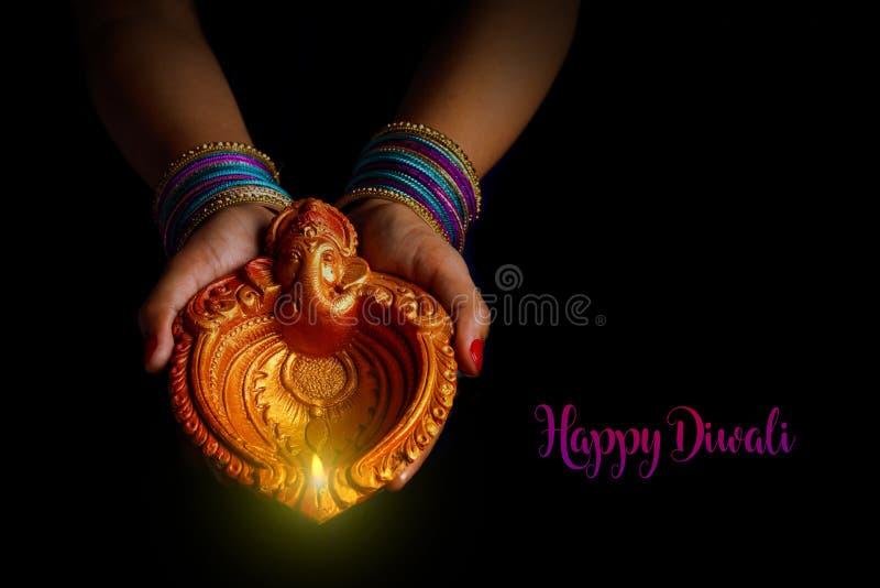 印度节日diwali,灯在手中 免版税库存图片
