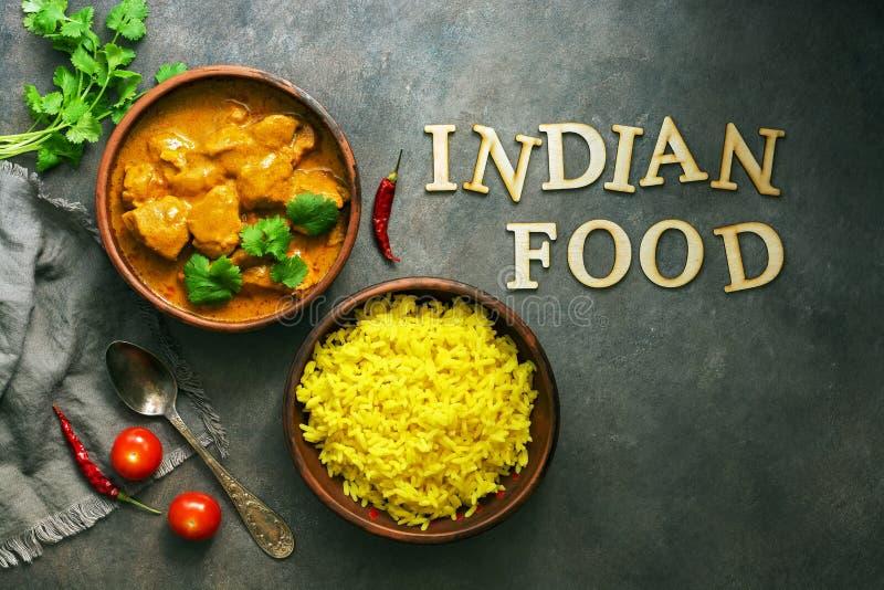 印度食物辣鸡tikka masala用在黑暗的背景的米 从木信件印度食物的Tex o 免版税库存图片