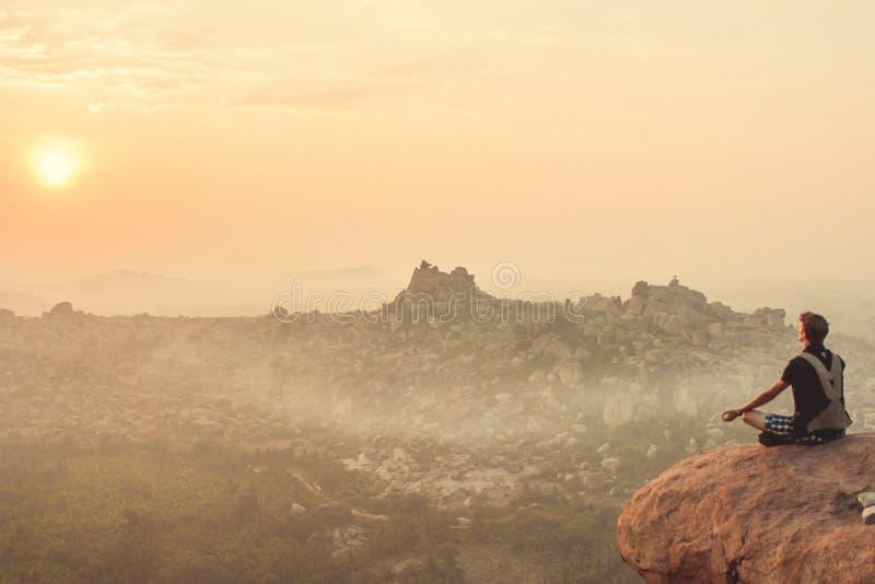 印度,亨比- 2015年12月22日:在黎明期间,一个人实践在峭壁的上面的瑜伽 免版税图库摄影