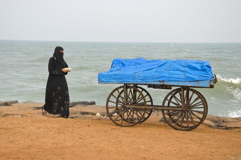 印度, Puducherry,由海和穆斯林妇女的流动摊位 免版税库存图片