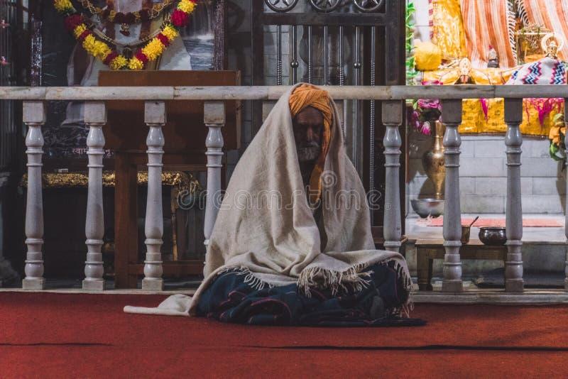 印度sadhu,坐在印度寺庙前面的圣洁者 免版税库存照片
