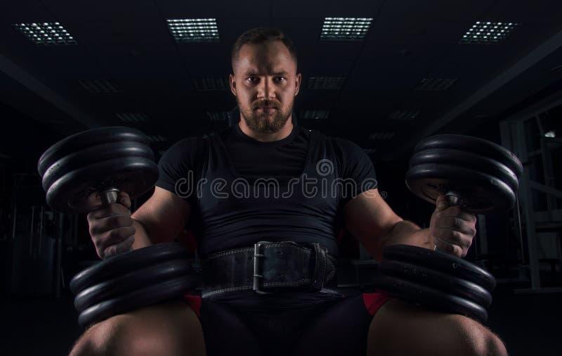 印象深刻的运动员坐与两个哑铃的一条长凳在他的腿 免版税图库摄影