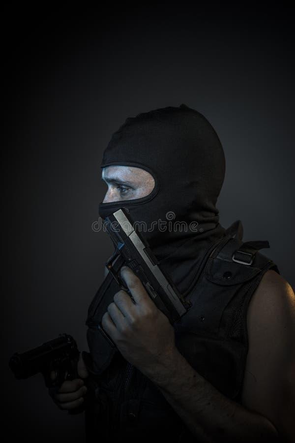 危险、凶手有摩托车盔甲的和枪 免版税图库摄影