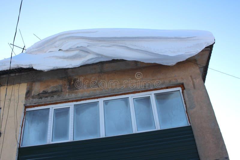 危险地垂悬在从房子的屋顶的窗口秋天期间的大雪漂泊 免版税图库摄影