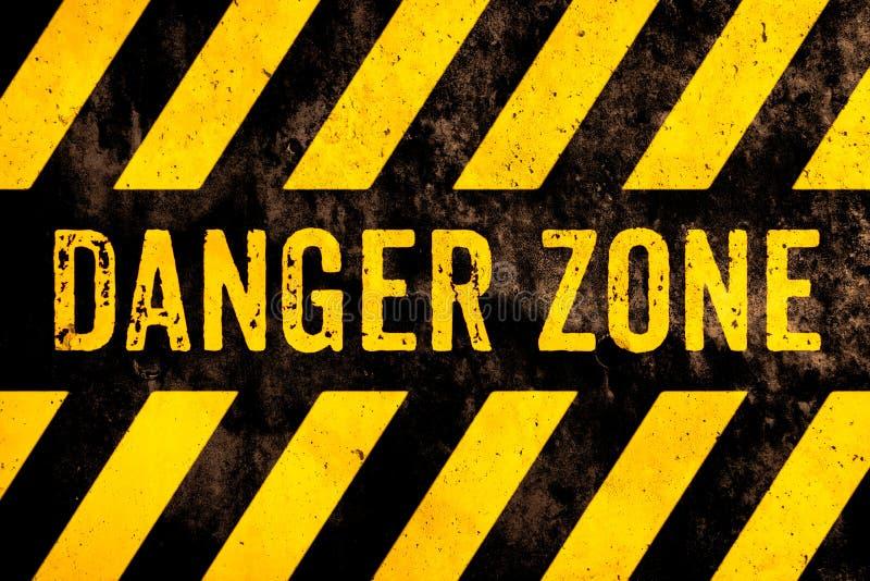 危险地带与黄色和黑条纹的警报信号文本被绘在混凝土墙表面门面水泥纹理背景 免版税库存照片