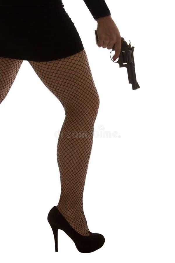 危险妇女的腿有手枪和黑鞋子剪影的 免版税库存照片